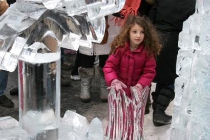 A little girl inspects an ice sculpture.